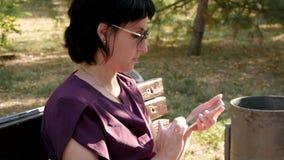 Uma menina moreno com óculos de sol senta-se em um banco em um parque do verão e em olhares na tela de seu telefone e toca-se no filme