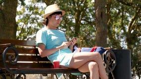Uma menina moreno em um chapéu e em um vestido senta-se em um banco de parque e usa-se o telefone, um vidro de suportes do café n filme