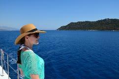 Uma menina moreno nova em um chapéu de palha, em óculos de sol e em uma túnica da praia de turquesa olha afastado na perspectiva  fotografia de stock