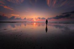 Uma menina mostrada em silhueta em uma praia Foto de Stock