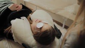 Uma menina muito bonita em um salão de beleza faz uma laminação chicoteia Colagem de espera nas pestanas a secar filme
