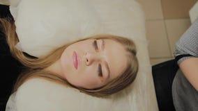 Uma menina muito bonita em um salão de beleza faz uma laminação chicoteia Colagem de espera nas pestanas a secar video estoque