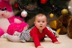 Uma menina muito pequena senta-se sob uma árvore de Natal com decorações coloridas Ano novo e árvore de Natal Fotografia de Stock Royalty Free
