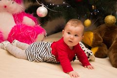 Uma menina muito pequena senta-se sob uma árvore de Natal com decorações coloridas Ano novo e árvore de Natal Fotos de Stock