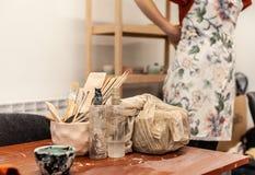 Uma menina na camisa vermelha que põe sobre a jardineira branca ao olhar fixamente no estúdio da cerâmica, ferramentas para a cer foto de stock royalty free
