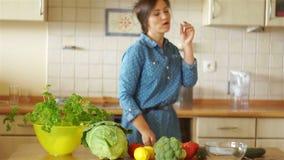 Uma menina na cozinha está tentando uma cenoura Está em um bom humor Os benefícios e o dano do vegetarianismo vídeos de arquivo