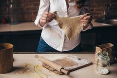 Uma menina na cozinha prepara uma massa Imagens de Stock Royalty Free