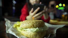 Uma menina na empresa de um homem que toma a imagens em seu smartphone seu hamburguer na barra video estoque