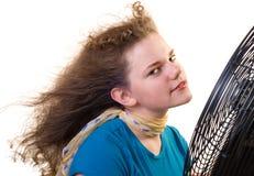 Uma menina na frente de um grande ventilador Foto de Stock Royalty Free