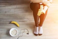 Uma menina nas calças justas está comendo uma banana, farinha de aveia, fones de ouvido fotografia de stock royalty free