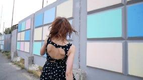 Uma menina nas sapatilhas e em um vestido está andando em torno da cidade filme