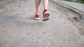 Uma menina nas sapatilhas e em um vestido está andando em torno da cidade video estoque