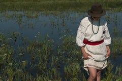Uma menina no bordado ucraniano com uma grinalda em sua cabeça pelo lago em um prado entre as flores Fotografia de Stock