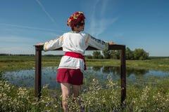Uma menina no bordado ucraniano com uma grinalda em sua cabeça pelo lago em um prado entre as flores Imagens de Stock