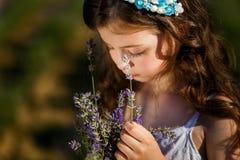 Uma menina no campo da alfazema no por do sol Flores de cheiro de uma alfazema da menina imagens de stock