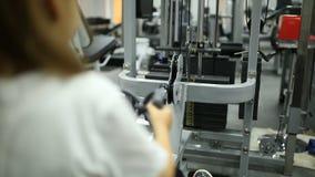 Uma menina no gym está exercitando no simulador vídeos de arquivo