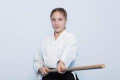 Uma menina no hakama preto que está na pose de combate com jo de madeira Fotos de Stock