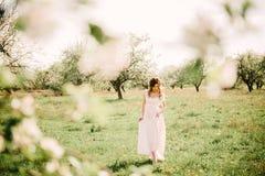 Uma menina no jardim de árvores de maçã de florescência Imagens de Stock