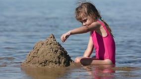 Uma menina no raso do rio enviou uma grande pilha da areia video estoque