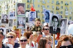 Uma menina no uniforme militar senta-se em ombros de seu pai no ` imortal do regimento do ` da ação no dia da vitória em Volgogra Fotos de Stock Royalty Free