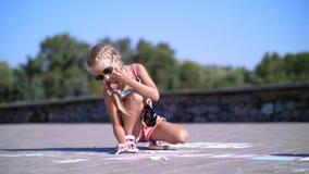 Uma menina nos óculos de sol, tira desenhos com os pastéis coloridos no asfalto, telhas da rua Um dia de verão quente video estoque