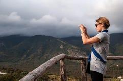 Uma menina nos óculos de sol toma uma foto das montanhas Imagens de Stock