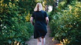 Uma menina nos sundress cinzentos que correm através do parque da câmera Modo despreocupado Verdes floresta filme