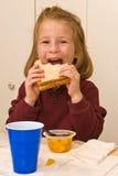 Menina nova da escola que come o almoço Fotografia de Stock Royalty Free