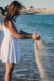 Uma menina nova, delgada está na costa do mar azul em um vestido curto branco, guarda a areia em suas mãos e derrama-a fotos de stock royalty free