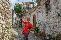 Uma menina nova do turista em uma blusa cor-de-rosa está estando em uma estrada cobbled na cidade albanesa antiga de Berat, negli imagens de stock