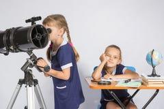 Uma menina olha através de um telescópio, a outra menina está esperando resultados tristes Fotografia de Stock Royalty Free