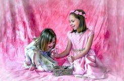Uma menina olha em um espelho guardado por sua irmã mais velha imagem de stock royalty free