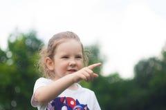 Uma menina olha na distância, diz algo e aponta um dedo foto de stock royalty free