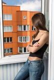 Uma menina olha para fora a janela Imagem de Stock Royalty Free