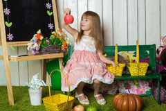 Uma menina olha um assento da maçã Fotos de Stock Royalty Free