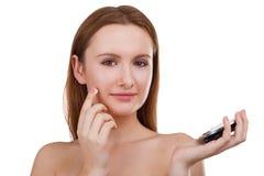 Uma menina põe um creme cosmético sobre sua cara Isolado no fundo branco foto de stock