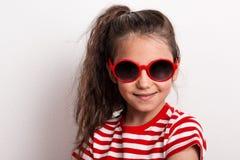 Uma menina pequena com óculos de sol vermelhos e o t-shirt listrado que estão em um estúdio Imagens de Stock Royalty Free