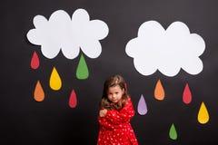 Uma menina pequena em um fundo preto com nuvens e pingos de chuva Imagens de Stock Royalty Free