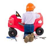 Uma menina pequena que repara o carro do brinquedo. imagens de stock