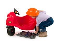 Uma menina pequena que repara o carro do brinquedo. fotos de stock royalty free