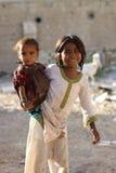 Uma menina pobre com seu Sistrer Fotos de Stock Royalty Free