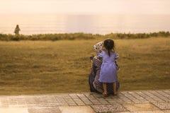 Uma menina que abraça sua mãe fotografia de stock