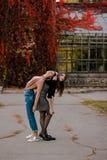 Uma menina que adere-se a sua amiga Estudantes bonitos tristes no parque do outono imagem de stock