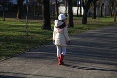 Uma menina que anda afastado Fotos de Stock