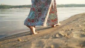Uma menina que anda ao longo da praia ao longo do Sandy Beach no por do sol Os pés de uma menina do close-up que anda ao longo da filme