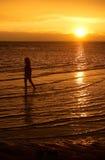 Uma menina que anda no beira-mar durante o por do sol Fotografia de Stock