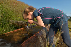 Uma menina que bebe a água natural fresca da mola da montanha Fotos de Stock Royalty Free