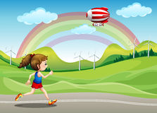 Uma menina que corre na estrada e em um dirigível acima dela Fotos de Stock