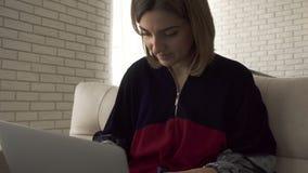 Uma menina que datilografa no telefone celular, a seguir sorrindo e datilografando em um portátil Datilografia fêmea no teclado F vídeos de arquivo