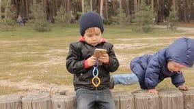 Uma menina que escala na cerca onde um menino se está sentando quem botões de impulsos no smartphone vídeos de arquivo